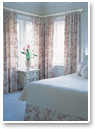 Use patterns smartly to pull together a room. Repeating the colour draws the eye through the room. Notice that we've used the same fabric on the curtains, throw pillows and bed skirt. We also repeated the red with a flowering plant.