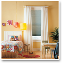 Add tab top curtain panels over cellular shades to soften edges and block sleep-robbing light from entering the bedroom.