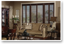 Real wood shutters in dark wood stains echo the dark wood in the furniture drawing the eye through the room and making it appear more interesting and larger.